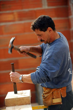 whittle: Worker using chisel and hammer on large block of wood