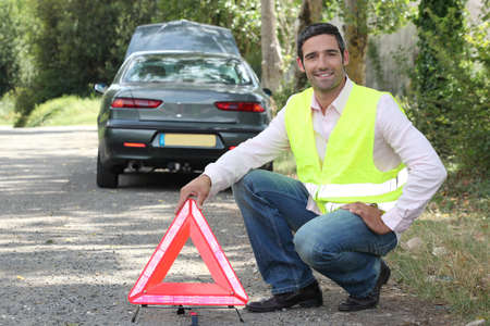 Man putting out a hazard triangle photo