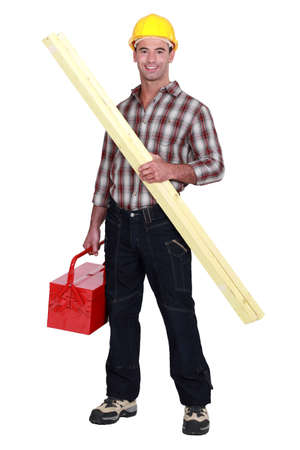 facing to camera: Tradesman holding a wooden plank and a toolbox