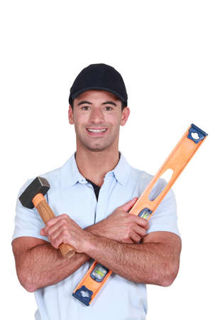 hairy arms: A handyman with a hammer and a level  Stock Photo