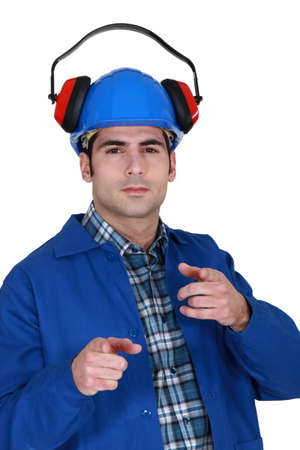 nuisance: portrait of helmeted craftsman with earmuffs showing off