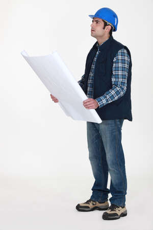 Tradesman examining a blueprint Stock Photo - 15624540