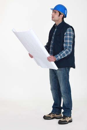 Tradesman examining a blueprint