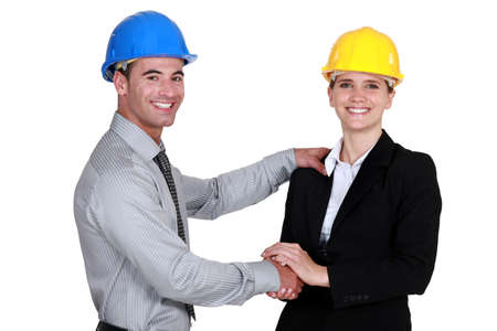 hard look: foreman shaking hands with female architect