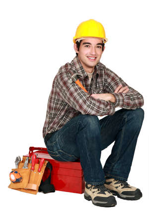 cross armed: portrait of young craftsman sitting on toolcase Stock Photo