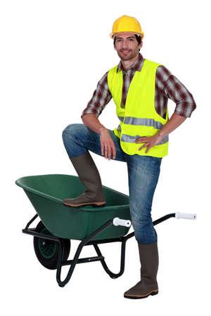 construction material: Man casually stood by empty wheelbarrow