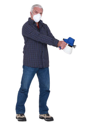 pressurized: Tradesman holding a spray gun and wearing a mask