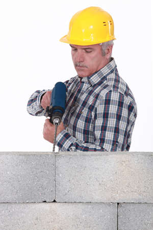 Construction worker with a masonry drill photo