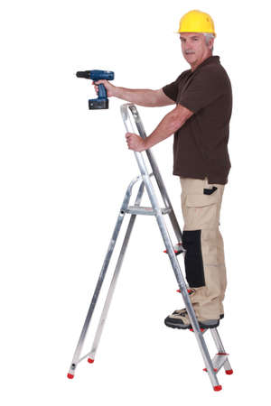 rungs: Tradesman using a power tool while standing on a stepladder Stock Photo