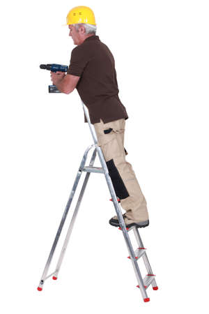 Senior carpenter stood up ladder with drill photo