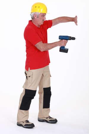 diligente: Tradesman usando una herramienta eléctrica