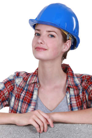 invariable: Female mason stood by unfinished  wall Stock Photo