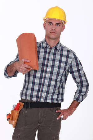 Handyman holding roof tiles photo