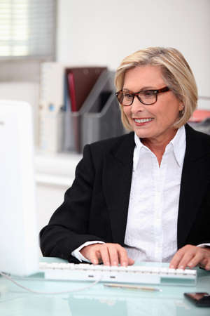 clerical: mature, woman,  typing Stock Photo