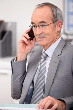 administrador de empresas: Hombre de 65 años vestido con un traje gris y llamando Foto de archivo