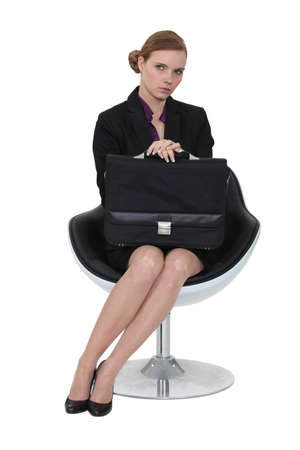 distant: Serious businesswoman sitting with a briefcase Stock Photo
