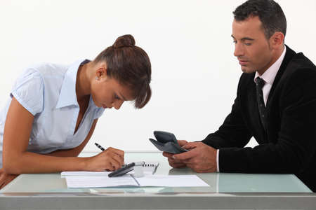 sums: A team of business professionals calculating their budget Stock Photo