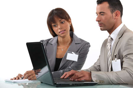 visitors: Two business visitors working with laptop Stock Photo