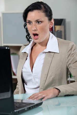 mad girl: businesswoman looking at her laptop open mouthed Stock Photo