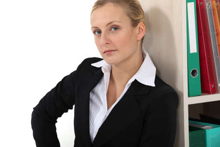 Businesswoman leaning against bookshelf photo