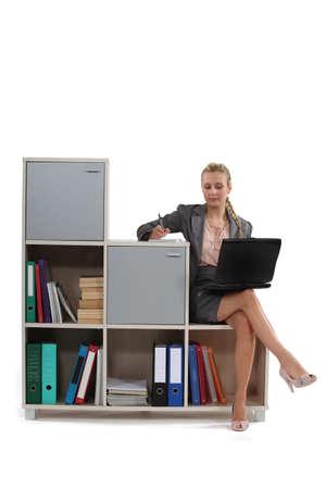 falda corta: Mujer sentada en mobiliario de oficina Foto de archivo