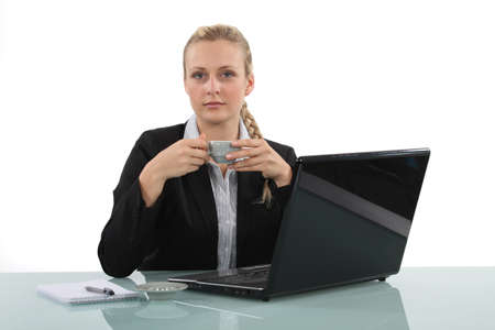 A businesswoman having a cup of coffee in her office  photo
