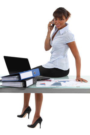 table skirt: Woman sitting on the table in the office Stock Photo