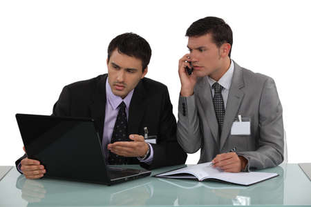 Two businessmen arguing at a desk photo