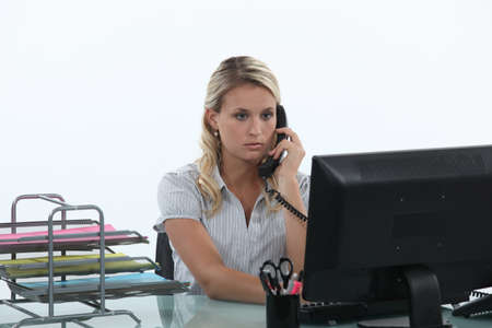 phonecall: Woman sitting at her desk on the phone Stock Photo