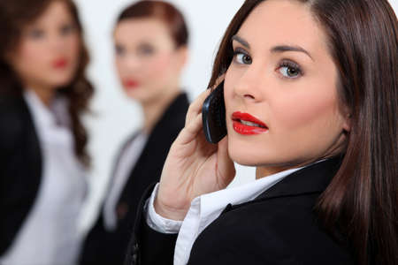 assertive: Businesswoman in red lipstick using a cellphone Stock Photo