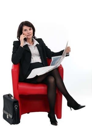 Businesswoman talking on her mobile phone while reading the newspaper photo