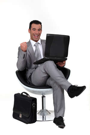 Successful man sat in chair with laptop photo