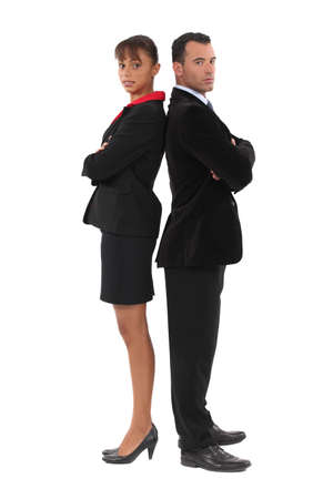 Businessman and businesswoman standing back-to-back photo