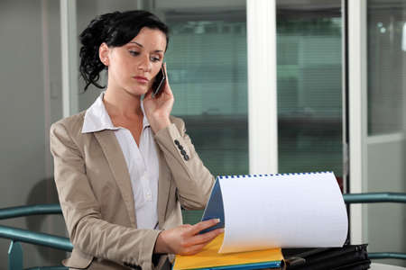 assignation: businesswoman talking on her cell and looking at her agenda Stock Photo