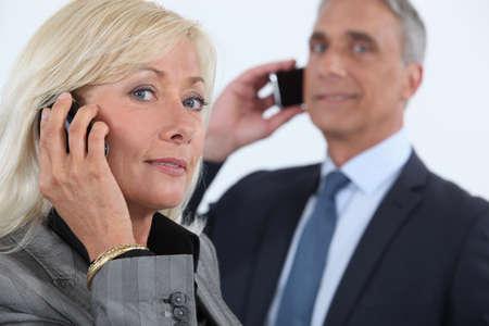 sexy mature women: Mature business couple using cellphones