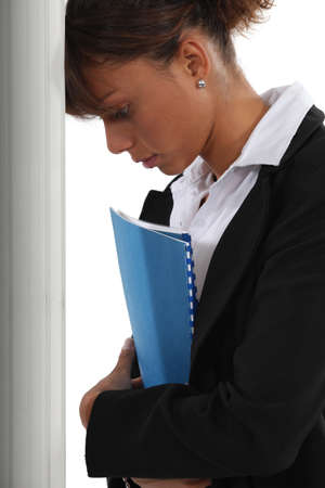 discrimination: Frustrated woman leaning her head against a wall Stock Photo