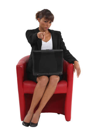 Businesswoman sat in chair pointing at camera Stock Photo - 15672536