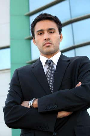 arrogant: Confident young businessman stood outside office
