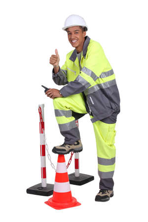 Man in high visibility overalls with a traffic cone and barrier photo