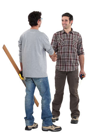 acknowledging: Two carpenters shaking hands