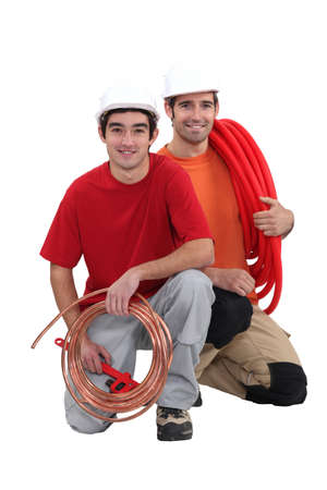 water damage: Plumbers with traditional copper and modern plastic pipe Stock Photo