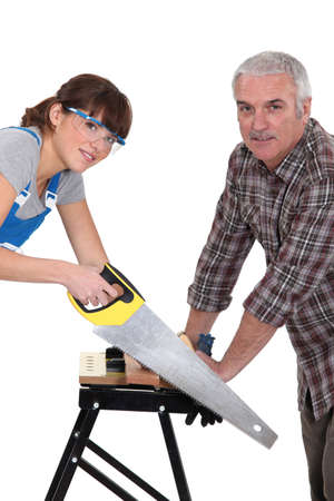 sawing: Father and daughter sawing plank of wood Stock Photo