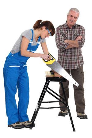 apprentice: Female apprentice sawing wood