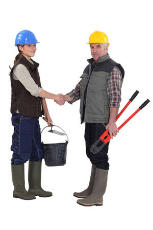 workmate: female apprentice shaking hands with mature workmate Stock Photo