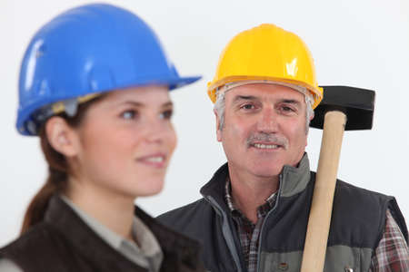 qualified worker: Construction worker with young female helper