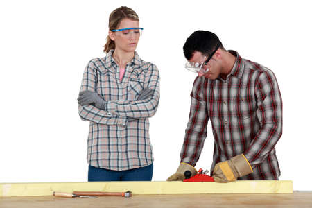 Man and woman using wood plane photo