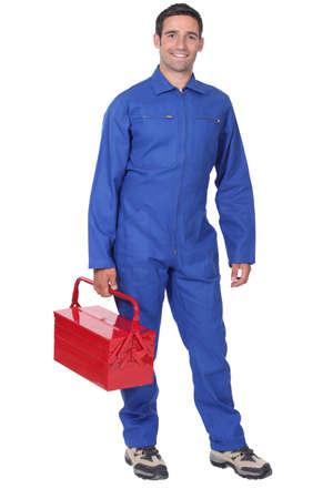 overol: El hombre vestido con un mono azul con caja de herramientas Foto de archivo