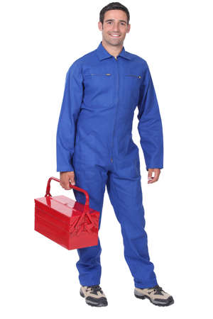 dungarees: Man wearing blue overalls holding tool kit