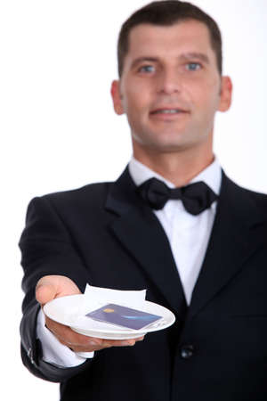 creditcard: Male waiter holding credit-card and receipt