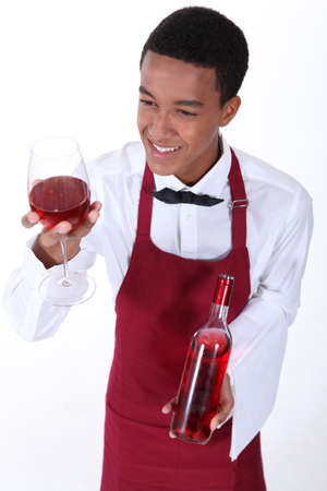Male waiter serving glass of rose